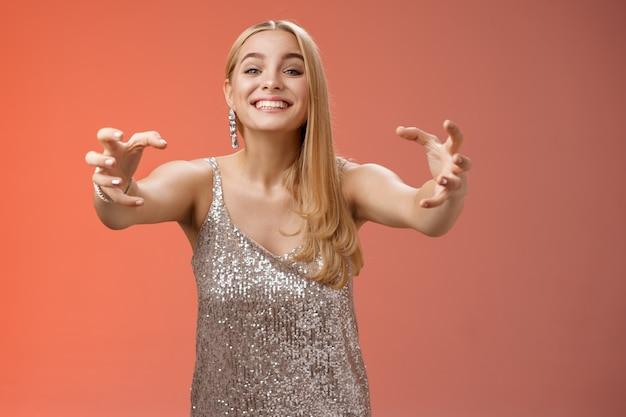 Podekscytowana, obsesyjna atrakcyjna, szalona blond kobieta w srebrnej sukience glamour uśmiechająca się dziwnie, podekscytowana, rozciągająca się dłoń jak pazury, która chce przytulić byłego chłopaka, który jest przywiązany, stojąc na czerwonym tle.