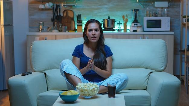 Podekscytowana pani wspierająca ulubionego gracza wieczorem oglądając telewizję w domu. fan sportu w piżamie krzyczy w telewizji podczas zawodów piłkarskich siedząc na kanapie w mieszkaniu przed telewizorem.