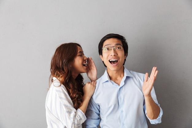 Podekscytowana para azjatyckich stojących na białym tle, opowiadających sobie sekrety