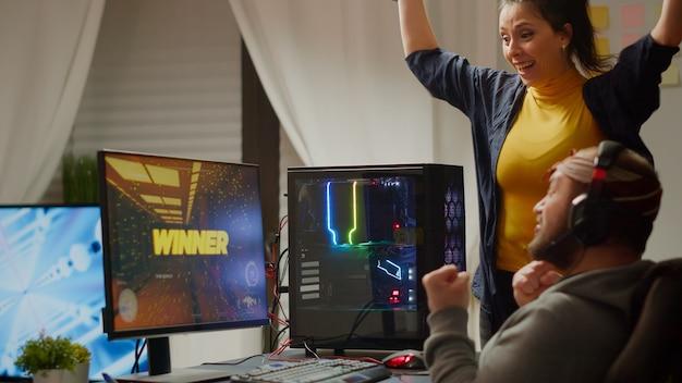 Podekscytowana para graczy wygrywająca internetową grę wideo fps na potężnym komputerze rgb, krzyczącym, podnoszącym ręce. procy cybernecy występujący podczas mistrzostw e-sportowych w grach noszących zestaw słuchawkowy