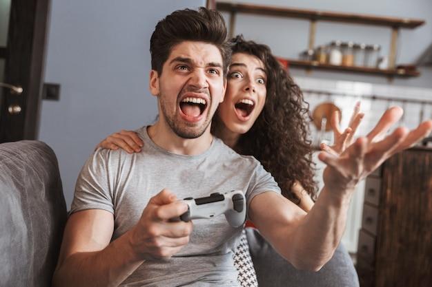 Podekscytowana para mężczyzna i kobieta w wieku 30 lat siedząca na kanapie w domu i grająca w gry wideo razem z joystickami