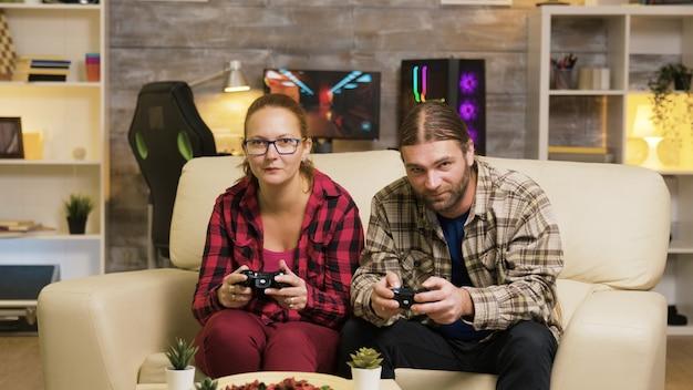 Podekscytowana para przybija piątkę podczas grania w gry wideo online, siedząc na kanapie za pomocą bezprzewodowych kontrolerów.