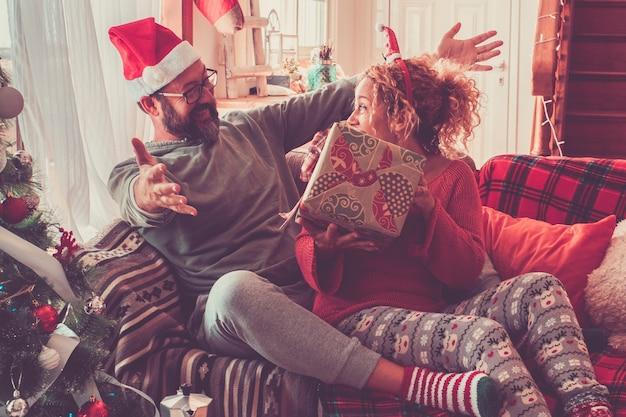 Podekscytowana para trzymając prezent w przeddzień bożego narodzenia w domu. caucasion para razem świętuje boże narodzenie w domu. ekstatyczny mężczyzna i kobieta z prezentem świątecznym na kanapie w domu