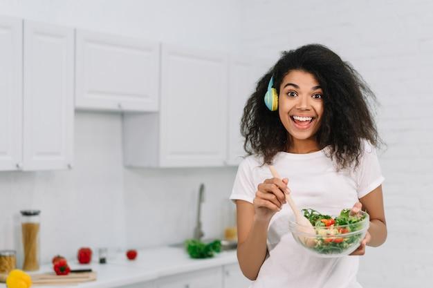 Podekscytowana piękna afroamerykanka gotuje wegetariański obiad w kuchni. szczęśliwa dziewczynka emocjonalność gospodarstwa pyskać ze świeżej sałatki, słuchanie muzyki w domu, śmiejąc się