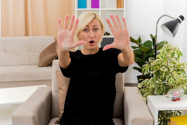 Podekscytowana piękna blondynka rosjanka siedzi na fotelu, wskazując palcami dziesięć w salonie