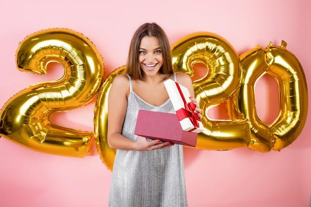 Podekscytowana piękna kobieta otwierając pudełko na prezent przed nowy rok 2020 balony na białym tle nad różowym