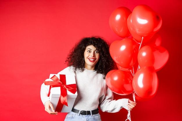 Podekscytowana piękna kobieta świętuje walentynki, trzymając pudełko i romantyczne balony w kształcie serca, patrząc zaskoczony na aparat, stojąc na czerwonym tle.