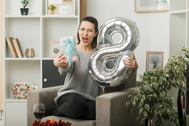 Podekscytowana piękna kobieta w szczęśliwy dzień kobiet trzymająca balon numer osiem z prezentem siedzącym na fotelu w salonie