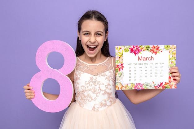 Podekscytowana piękna mała dziewczynka na szczęśliwy dzień kobiety trzymająca numer osiem z kalendarzem odizolowanym na niebieskiej ścianie