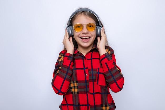 Podekscytowana piękna mała dziewczynka ubrana w czerwoną koszulę i okulary ze słuchawkami na białej ścianie