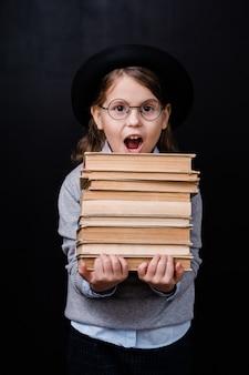 Podekscytowana podstawowa uczennica w kapeluszu i okularach niosąca stos książek przeciwko czarnej przestrzeni w izolacji