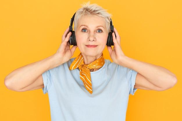 Podekscytowana pozytywna kobieta w średnim wieku z krótkimi farbowanymi włosami i niebieskimi oczami pozuje na białym tle w słuchawkach bezprzewodowych, ciesząc się przyjemną muzyką