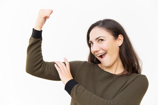 Podekscytowana pozytywna kobieta wyginająca i dotykająca bicepsa