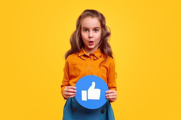 Podekscytowana preteen dziewczyna w kolorowym, swobodnym stroju, pokazująca sieć społecznościową, taką jak znak, stojąc