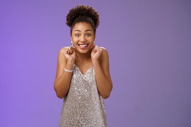 Podekscytowana przystojna szczęśliwa szczęśliwa afro-amerykańska kobieta wygrywająca pieniądze na loterii kasyno stojąca rozbawiona zachwycona chce spróbować więcej uśmiechniętych szeroko tańczących zaciskających pięści radować triumf.