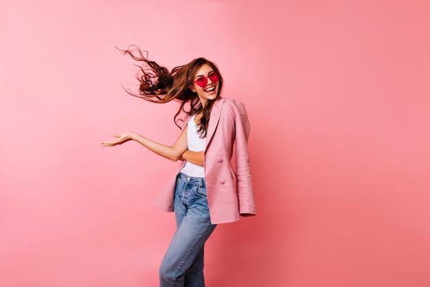 Podekscytowana przystojny dziewczyna tańczy w okularach przeciwsłonecznych. radosna imbirowa kobieta pozuje na różowo z macha włosami.