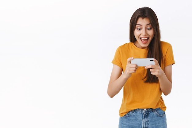 Podekscytowana, radosna, ładna kobieta w żółtej koszulce grająca w niesamowitą zabawną nową grę mobilną, trzymająca smartfon poziomo, wiwatująca, uśmiechnięta i zdumiona wyświetlaczem telefonu