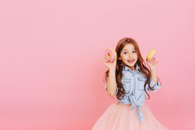 Podekscytowana radosna młoda ładna dziewczyna w tiulowej spódnicy wyrażająca pozytywne nastawienie, zabawy z aparatem z pączkami na białym tle na różowym tle. szczęśliwe dzieciństwo z smacznym deserem. umieść tekst fot