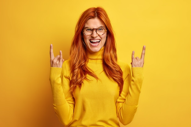 Podekscytowana, radosna ruda kobieta pokazuje gest rock and rolla, rogi z palcami śmieje się radośnie, lubi słuchać ulubionej muzyki rockowej, ubrana w swobodny golf.