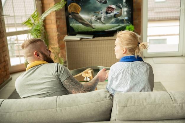 Podekscytowana rodzina ogląda mistrzostwa futbolu amerykańskiego, mecz sportowy w domu. piękna para kaukaska dopingująca drużynę narodową z tłumaczeniem. pojęcie ludzkich emocji, wsparcia, zabawy.