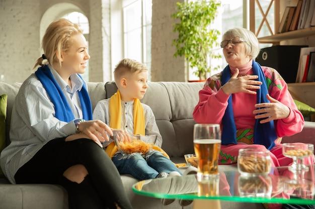 Podekscytowana rodzina ogląda piłkę nożną, mecz sportowy w domu. babcia, mama i syn kibicują narodowej koszykówce, piłce nożnej, tenisowi, piłce nożnej, drużynie hokejowej. pojęcie emocji, wsparcia, dopingu.