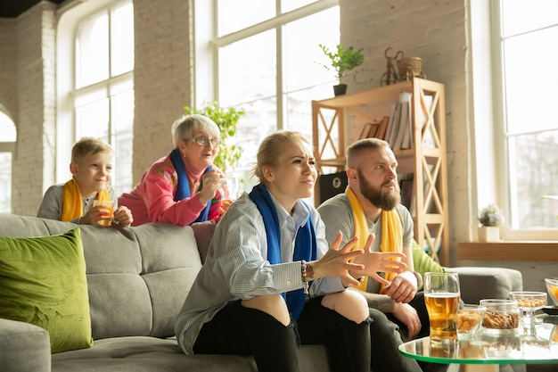 Podekscytowana rodzina ogląda piłkę nożną, mecz sportowy w domu. dziadkowie, rodzice i dziecko dopingują ulubioną narodową drużynę koszykówki, piłki nożnej, tenisa, piłki nożnej, hokeja. pojęcie emocji, wsparcie.