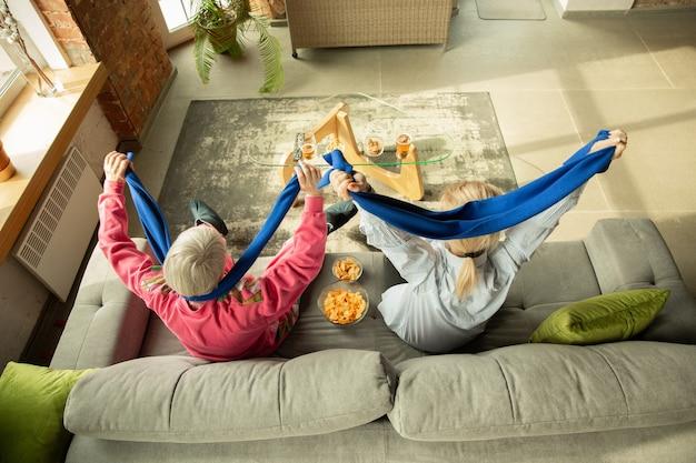 Podekscytowana rodzina ogląda piłkę nożną, mecz sportowy w domu. emocjonalne kibicowanie babci i córce dla narodowej koszykówki, piłki nożnej, tenisa, piłki nożnej, drużyny hokejowej. pojęcie emocji, wsparcia, dopingu.