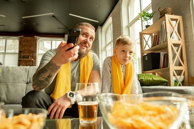 Podekscytowana rodzina ogląda piłkę nożną, mecz sportowy w domu. ojciec i syn szukają kanału telewizyjnego z narodową koszykówką, piłką nożną, tenisem, piłką nożną, drużyną hokejową. pojęcie emocji, wsparcia, dopingu.