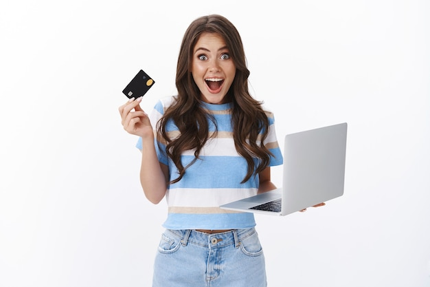 Podekscytowana, rozbawiona, ładna kobieta trzyma laptop i kartę kredytową, uśmiechnięta zafascynowana, gotowa zapłacić za zakupy, przeglądająca internet, kupująca gadżety online, uwielbia, jak łatwe zakupy w jej banku