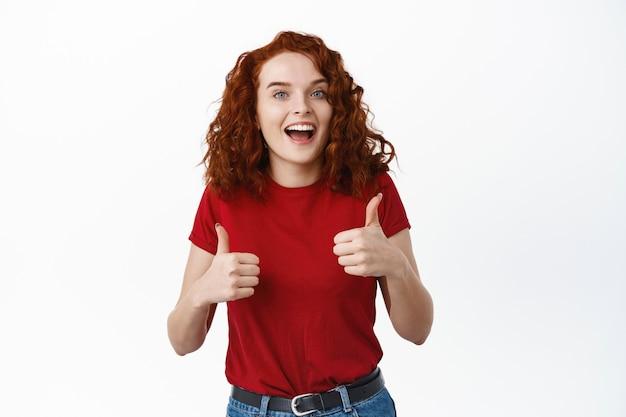 Podekscytowana ruda dziewczyna chwaląca dobrą robotę, pokazująca kciuki w górę i uśmiechnięta zadowolona, kiwa głową z aprobatą i mówi tak, udziela pozytywnej odpowiedzi, stojąc przy białej ścianie