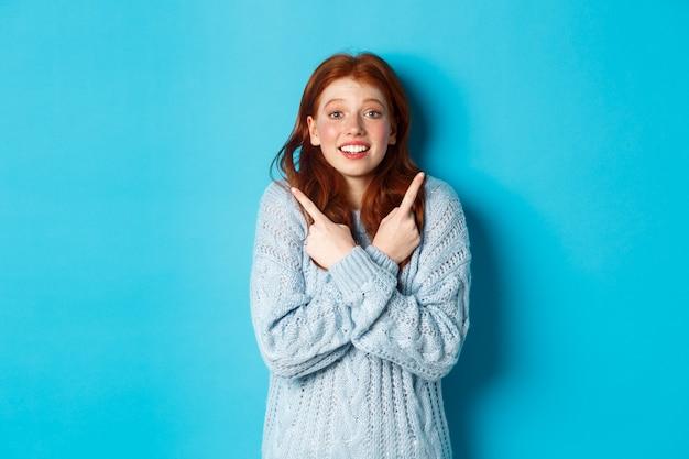 Podekscytowana ruda dziewczyna wskazująca palcami w bok, pokazująca dwie możliwości i kusząca spojrzenie na aparat, stojąca na niebieskim tle