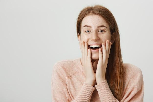 Podekscytowana ruda dziewczyna wygląda na pochlebioną lub wzruszoną, uśmiechając się zaskoczoną