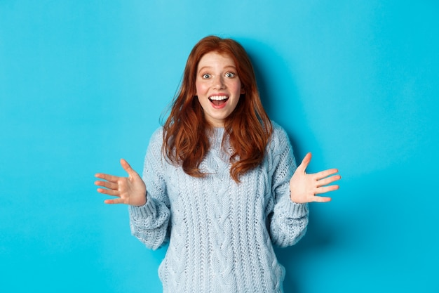 Podekscytowana ruda kobieta ściska dłonie, wyjaśnia ważne wieści, wpatruje się w kamerę ze zdumieniem, stoi na niebieskim tle.