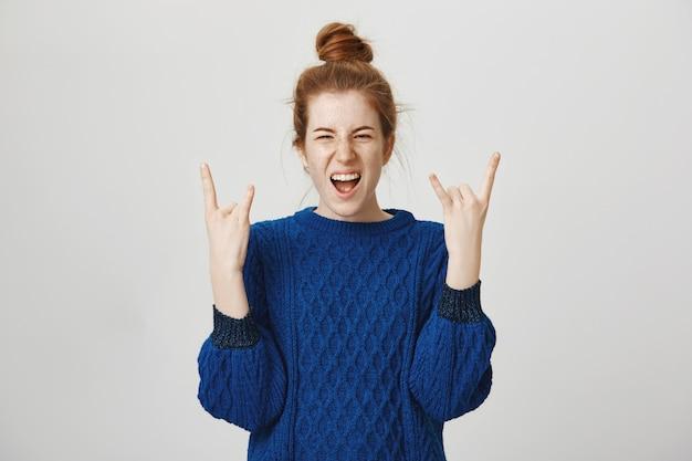 Podekscytowana ruda nastolatka bawi się, pokazując gest rock-n-roll