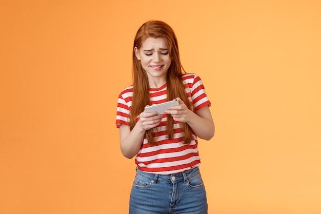 Podekscytowana rudowłosa kaukaska dziewczyna wygląda intensywnie marszcząc brwi, próbując przejść trudny poziom gry, grając w nową grę zręcznościową ...