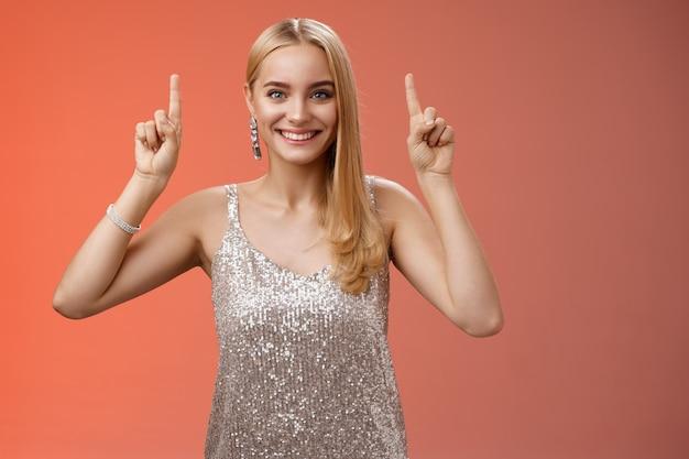 Podekscytowana śliczna blond europejka w srebrnej błyszczącej eleganckiej sukience podnosi ręce w górę pokazując imponującą niesamowitą reklamę uśmiechnięta radośnie podekscytowana chce przyjrzeć się bliżej, czerwone tło.