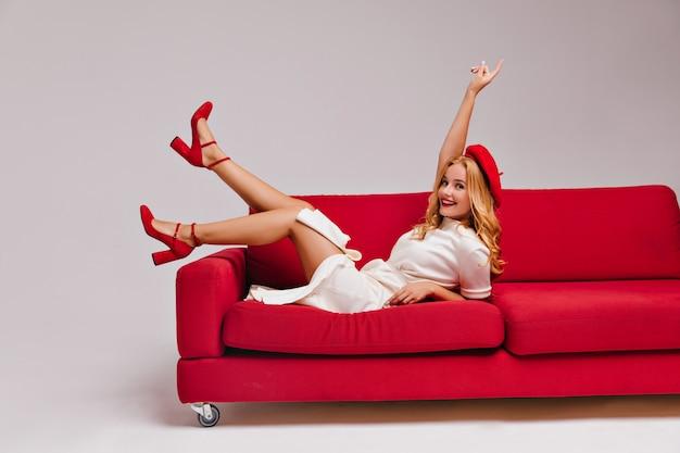 Podekscytowana śliczna dziewczyna w czerwonym berecie, dobra zabawa przyjemna europejska kobieta w sukni i butach na wysokim obcasie, leżąc na trenerze.
