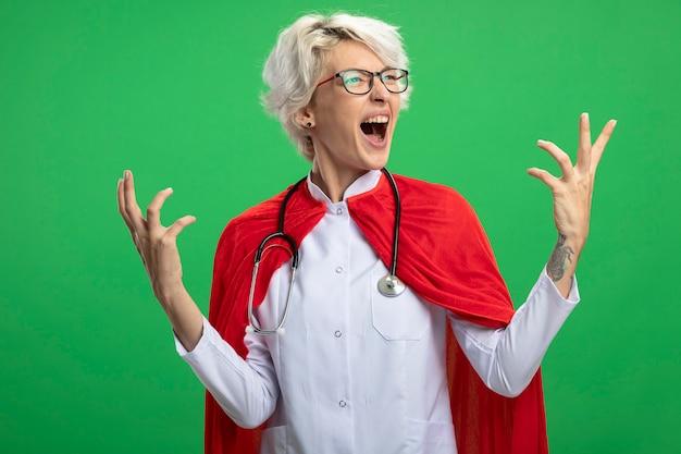 Podekscytowana słowiańska superbohaterka w mundurze lekarza z czerwoną peleryną i stetoskopem w okularach optycznych