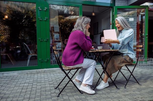 Podekscytowana starsza azjatycka kobieta otwiera prezent prezentowany przez najlepszego przyjaciela na tarasie kawiarni na świeżym powietrzu