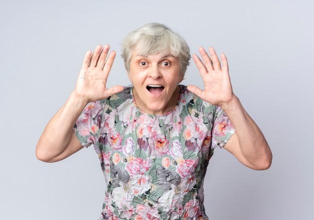Podekscytowana starsza kobieta stoi z uniesionymi rękami na białym tle na białej ścianie