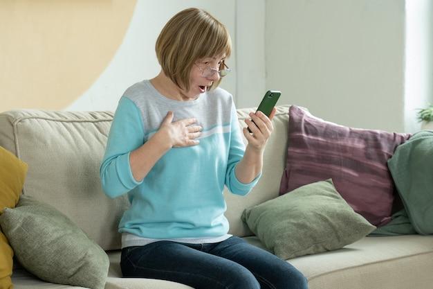 Podekscytowana starsza kobieta zaskoczona dobrymi niewiarygodnymi wiadomościami, patrząc na ekran smartfona siedzącego na kanapie w domu