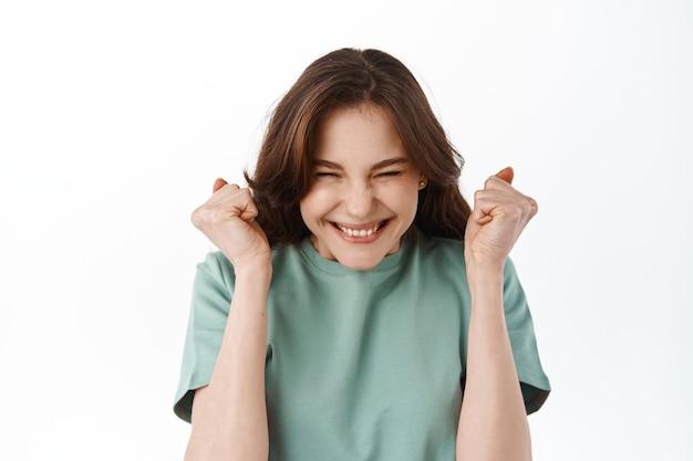 Podekscytowana studentka świętująca, skacząca ze szczęścia i radości, podnosząca ręce do góry i uśmiechająca się, triumfująca zwycięstwo i sukces, stojąca nad białą ścianą