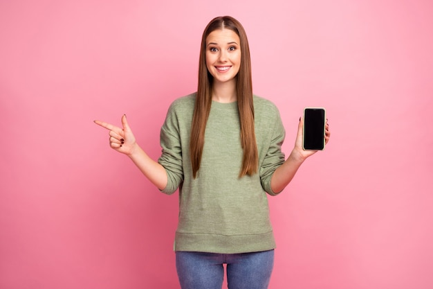 Podekscytowana stylowa dziewczyna trzyma telefon komórkowy wskazuje punkt palec copyspace