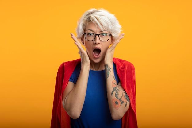 Podekscytowana superwoman w czerwonej pelerynie w okularach optycznych kładzie ręce na twarzy odizolowanej na pomarańczowej ścianie