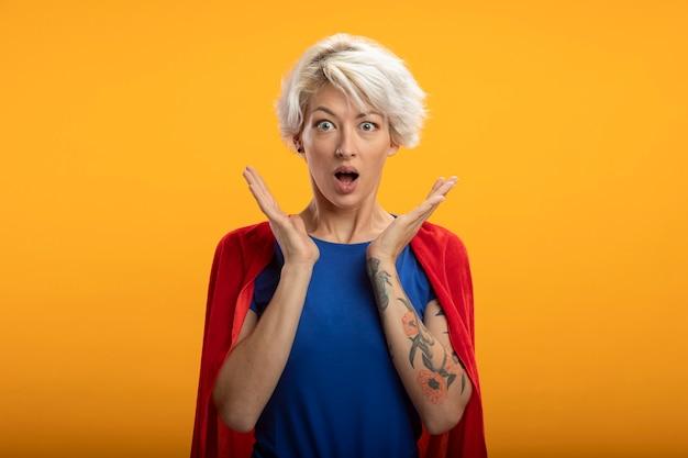 Podekscytowana superwoman z czerwoną peleryną stoi z podniesionymi rękami na białym tle na pomarańczowej ścianie