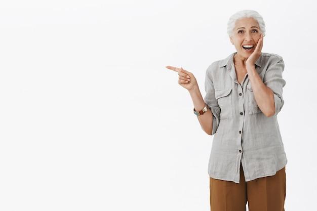 Podekscytowana szczęśliwa babcia wskazująca palcem w lewo i uśmiechnięta zdumiona