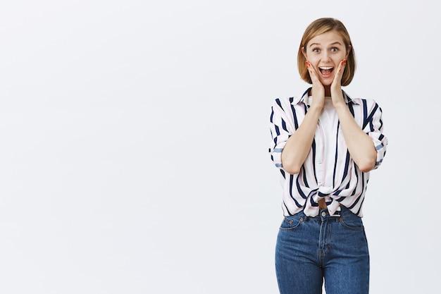 Podekscytowana szczęśliwa blond dziewczyna wyglądająca na rozbawioną i zachwyconą wspaniałą wiadomością