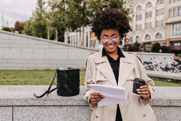 Podekscytowana szczęśliwa ciemnoskóra kobieta w beżowym trenczu i okularach uśmiecha się, trzyma na zewnątrz kartki papieru i szklankę do kawy