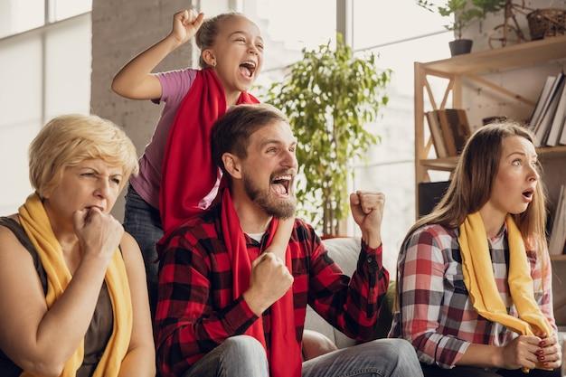 Podekscytowana, szczęśliwa duża rodzina ogląda piłkę nożną, piłkę nożną, koszykówkę, hokej, tenis, mecz rugby na kanapie w domu. fani dopingują emocjonalnie ulubioną drużynę narodową. sport, telewizja, mistrzostwa.
