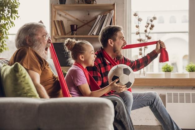 Podekscytowana, szczęśliwa duża rodzina oglądająca mecz piłki nożnej na kanapie w domu. fani dopingują emocjonalnie ulubioną drużynę narodową. zabawa od dziadka do córki. sport, telewizja, mistrzostwa.